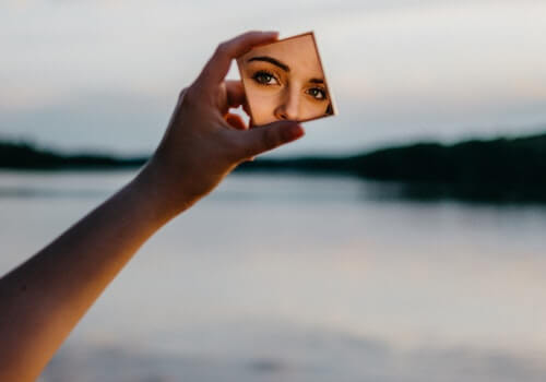 mujer-mirandose-espejo-cerca-lago